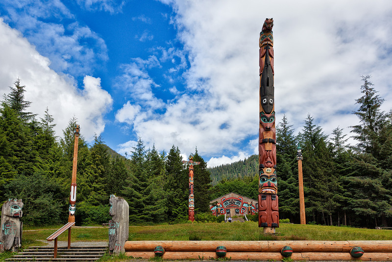 "Saxman Totem Park was begun in the late 1930's as a Civilian Conservation Corps (CCC) project.  It is the finest display of totem poles (28 in all) in Southeast Alaska.  Saxman village was settled by Tlingit people from the villages of Tongass and Cape Fox at the southern tip of Alaska.  Note the ""Frog Wall"" in the foreground and the ""Beaver Clan House"" in the background.<br /> Ketchikan, AK.<br /> July 15, 2010."