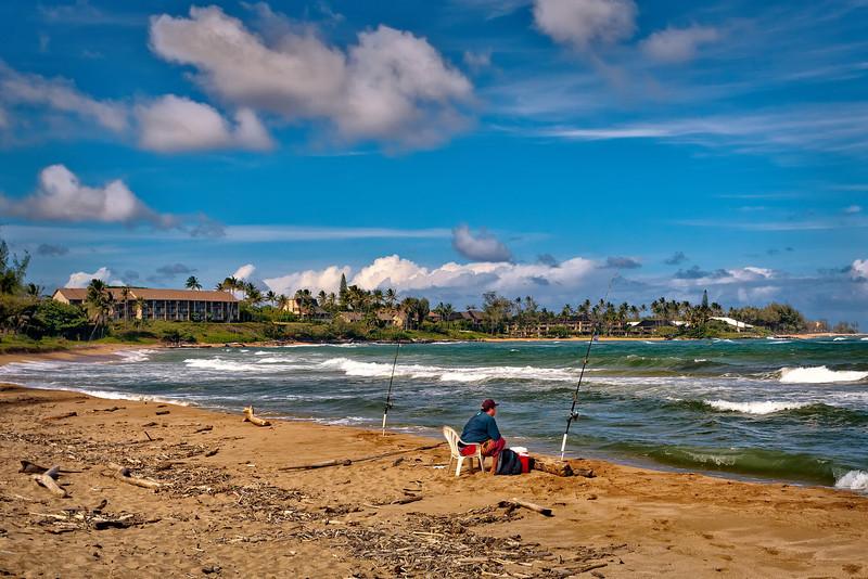 Kauai: Man fishing on the beach located behind the shopping district in Kapaa.