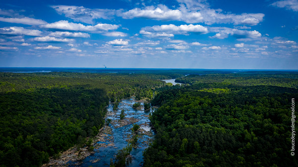 Looking down river from the Hwy 64 bridge, the Haw show off its rocky underbelly. In the background she merges with Lake Jordan.  The Harris Nuclear Plant in the distance is north of the Cape Fear River, the result of the Haw and Deep rivers merging 2 miles SW of the plant. ll May 14, 2020