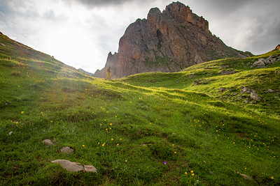 Hiking through verdent green meadows under craggy peaks in the Massif des Cerces in France.