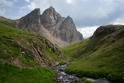 Open green meadows are punctuated with massive peaks in the Massif des Cerces in France.