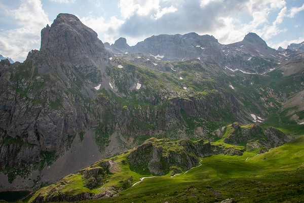 A stream cuts down through the verdant green meadows and rugged peaks of the Massif des Cerces in France.