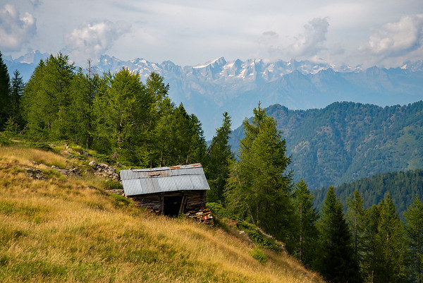 A humble structure on a grassy ridge looking towards the mighty peaks of the Bregaglia Range in northern Italy.