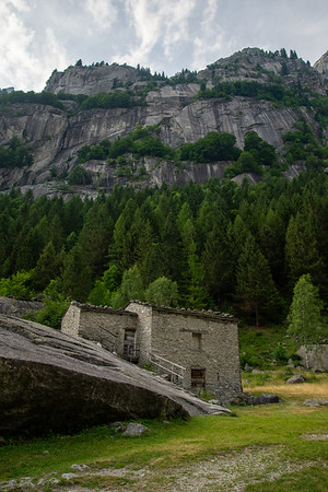 A refuge built into the rock under tall granite cliffs on a hot, muggy afternoon in the Italian Alps.