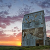 """Grainville, Idaho""<br /> <br /> About This Image:  The spring sun sets behind one of the few remaining buildings of Grainville, Idaho.    <br /> <br /> Photographs Available:  See the drop down menu to the upper right for a list of print sizes and prices for this photo."