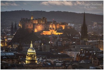 Edinburgh Castle and Old College dome floodlit, from Salisbury Crags