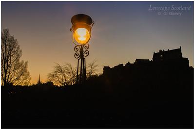 Princes Street lamp and Edinburgh Castle silhouette at dawn