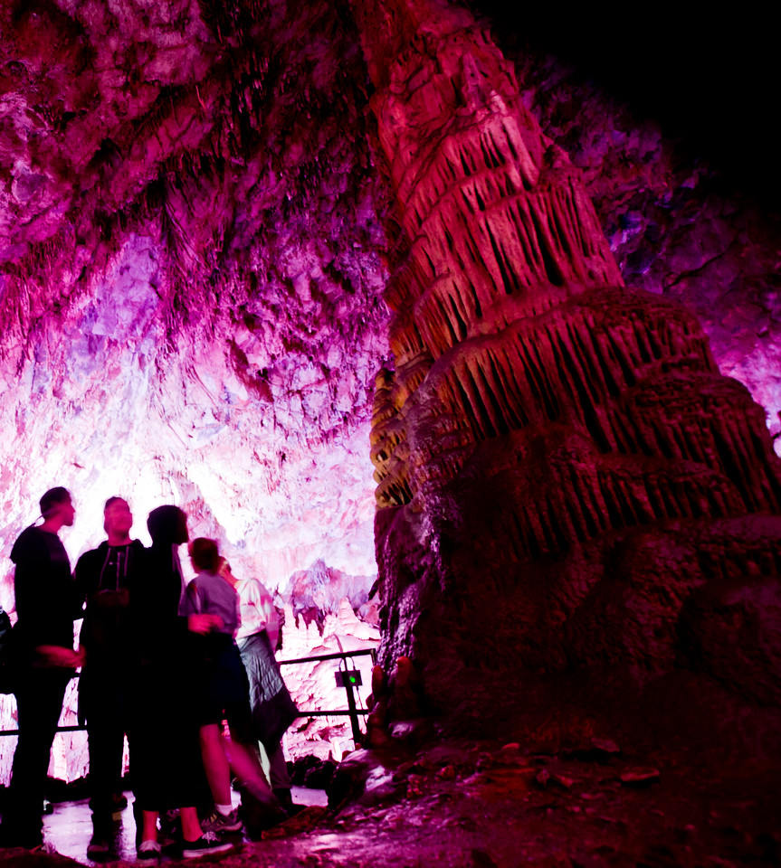 Tourists stand next to a large calcite stalagmite