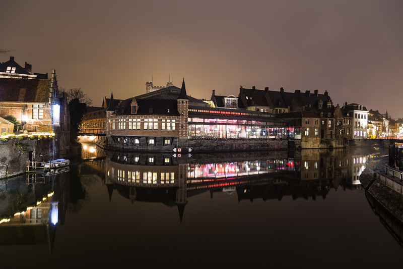 GHENT, BELGIUM - 18TH FEBRUARY 2016: A view of the outside of the De Oude Vismijn restaurant showing reflections in the river Leie at night.