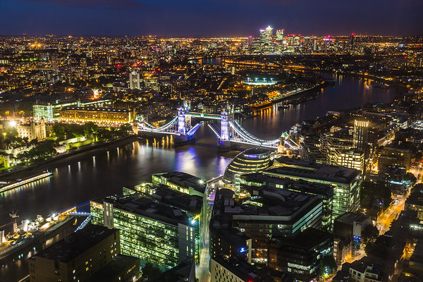 A high view towards Tower Bridge and Canary Wharf at night