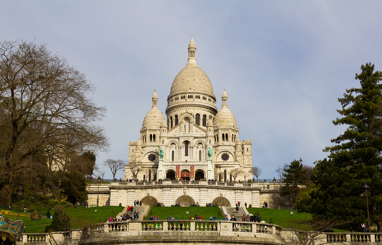 PARIS, FRANCE - 19TH MARCH 2014: The Sacré-Cœur during the day with people outside on the benches