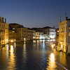 A view of colourful buildings along the Grand Canal in Venice.  The blurred motion of boats can be seen in the water