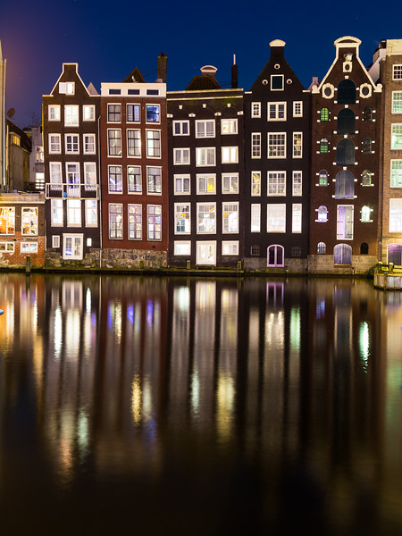 Buildings along the Damrak at Night in Amsterdam