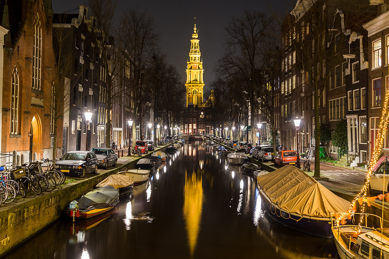 A view along the Groenbuigwal canal towards the Zuiderkerk church at night. Cars, boats and buildings can be seen.