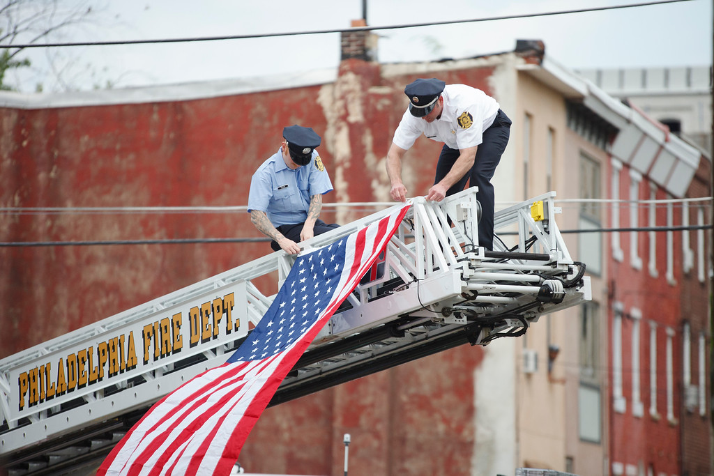 The Philadelphia Police and Fire Department unfurl a flag at a memorial ceremony in the Kensington neighborhood.