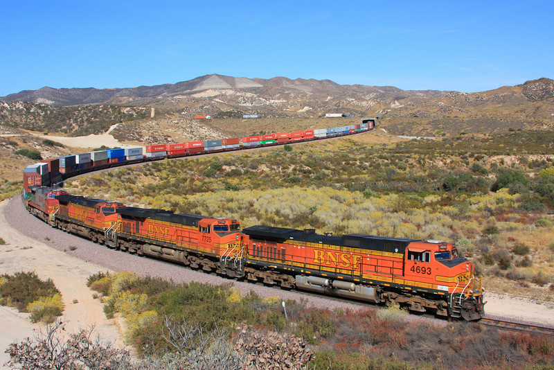 """One Train Equals No Trucks"" - A Burlington Northern Santa Fe train of highway freight containers is descending the grade at Cajon Junction, California into the Los Angeles basin. The journey began in Chicago, Illinois and consists of nearly 400 containers that would of otherwise been transported by truck, therefore, saving millions of gallons of fuel, generating less pollution and making the highways safer. Once arriving at Port of Long Beach (CA), the containers will be loaded onto ships so that they can reach their final destination overseas."