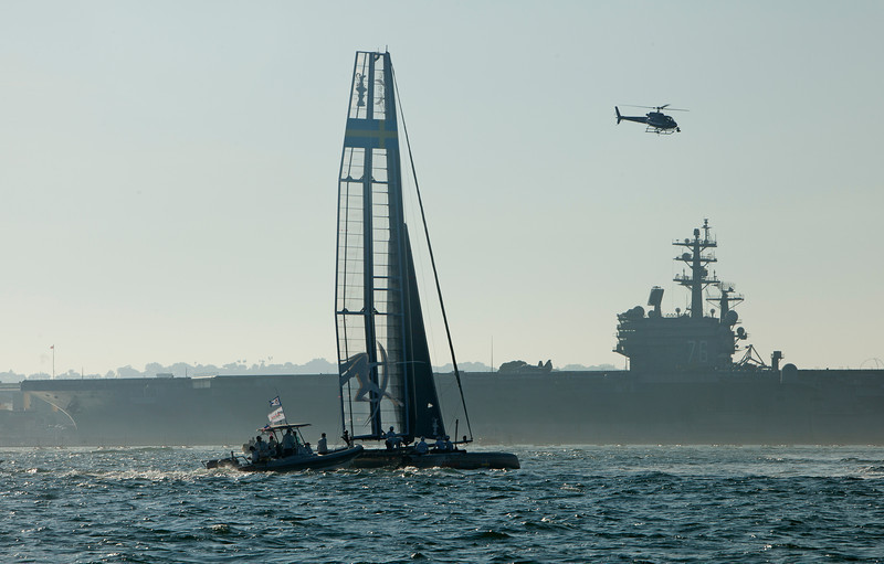 The America's Cup Trials in San Diego harbor, in AC45 Catamarans.  Artemis sails by an aircraft carrier, with a media helicopter above.