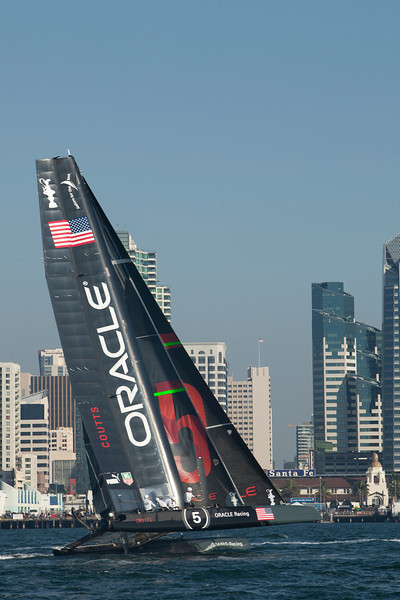 The America's Cup Trials in San Diego harbor, in AC45 Catamarans. The US entry flies a hull in front of the San Diego downtown skyline.
