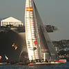 The America's Cup Trials in San Diego harbor, in AC45 Catamarans. Green.com crosses in front of the USS Midway during speed trials.
