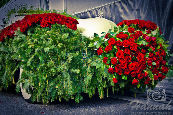 Vintage car covered with red roses and pine tree leaves during the  Portland Rose Festival 2011 Grand Floral Parade Float Showcase  © Copyright Hannah Pastrana Prieto
