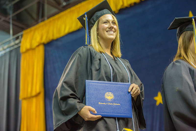 """Erin Otness smiles to her family in the crowd after accepting her bachelor's degree in elementary education during UAF's commencement ceremony May 11 in the Carlson Center.  <div class=""""ss-paypal-button"""">Filename: GRA-14-4186-0739.jpg</div><div class=""""ss-paypal-button-end"""" style=""""""""></div>"""
