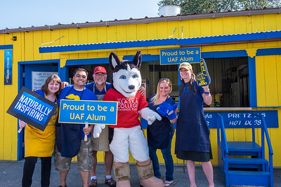 UAF alums Meredith Cameron, Mike Campbell, Todd Paris, Kristin Waggoner and Kristin Sullivan enjoy a visit from Dash the husky during their shift at the Alumni Burger Booth at the 2015 Tanana Valley State Fair.  Filename: DEV-15-4596-031.jpg
