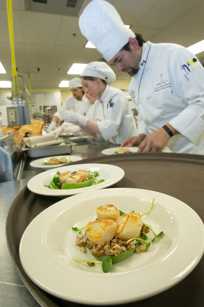 """Supervisor Luis Manuel leads a team of student chefs in preparing plates of Alaskan scallops being served to guests at the annual CTC culinary scholarship banquet in the Hutchison Institute of Technology.  <div class=""""ss-paypal-button"""">Filename: DEV-12-3383-112.jpg</div><div class=""""ss-paypal-button-end"""" style=""""""""></div>"""