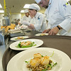 "Supervisor Luis Manuel leads a team of student chefs in preparing plates of Alaskan scallops being served to guests at the annual CTC culinary scholarship banquet in the Hutchison Institute of Technology.  <div class=""ss-paypal-button"">Filename: DEV-12-3383-112.jpg</div><div class=""ss-paypal-button-end"" style=""""></div>"