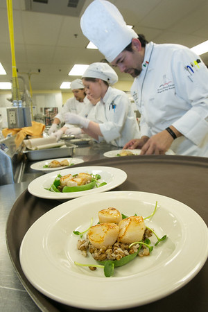Supervisor Luis Manuel leads a team of student chefs in preparing plates of Alaskan scallops being served to guests at the annual CTC culinary scholarship banquet in the Hutchison Institute of Technology.  Filename: DEV-12-3383-112.jpg