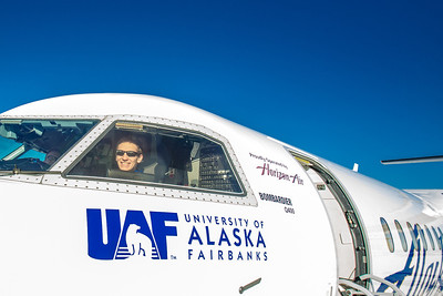 Michael Liuzza, a senior on the Nanooks rifle team, checks out the cockpit while touring one of the newest planes in the Alaska Airlines fleet, a Bombardier Q400 turboprop, which features the Alaska Nanooks and UAF.  Filename: DEV-14-4080-135.jpg