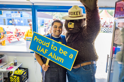 UAF Alumni Association board member Mike Campbell enjoys a visit from another celebrity during his shift in the Alumni Burger Booth at the 2015 Tanana Valley State Fair.  Filename: DEV-15-4596-035.jpg