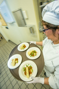 Rose Estrada carries a tray of manicotti being served to guests at the annual CTC culinary scholarship banquet in the Hutchison Institute of Technology.  Filename: DEV-12-3383-209.jpg