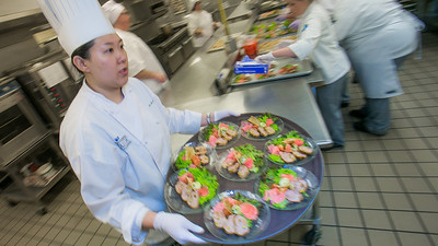 Yun Ji Hong carries a tray of salads being served to guests at the annual CTC culinary scholarship banquet in the Hutchison Institute of Technology.  Filename: DEV-12-3383-138.jpg