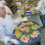 Yun Ji Hong carries a tray of salads being served to guests at the annual CTC culinary scholarship banquet in the Hutchison Institute of Technology.
