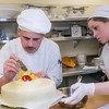 "Daniel Martolano and Melissa Raimer put the finishing touches on their cake before offering it to the highest bidder during the CTC Culinary Arts scholarship banquet at the Hutchison Institute of Technology.  <div class=""ss-paypal-button"">Filename: DEV-12-3383-015.jpg</div><div class=""ss-paypal-button-end"" style=""""></div>"