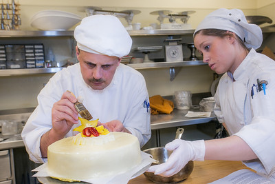 Daniel Martolano and Melissa Raimer put the finishing touches on their cake before offering it to the highest bidder during the CTC Culinary Arts scholarship banquet at the Hutchison Institute of Technology.  Filename: DEV-12-3383-015.jpg