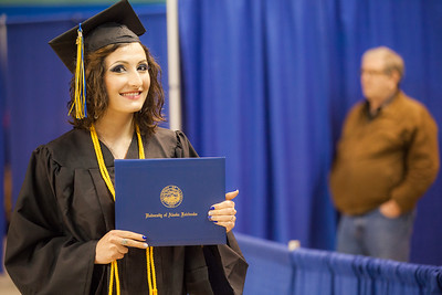 UAF journalism graduate Elena Sudduth pauses for a photo with her diploma cover during the 2015 commencement ceremony at the Carlson Center.  Filename: GRA-15-4539-455.jpg