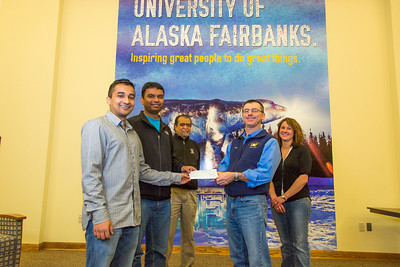 Chaitanya Borade, left, and  Vamshi Avandhula  present a check to UAF United Way campaign chair Mike Earnest after raising funds through the Namaste India student club-sponsored Diwali festival on campus. In back are Prof. Shirish Patil, founder and faculty advisor, and Amanda Wall, United Way campaign co-chair.  Filename: DEV-13-4000-6.jpg
