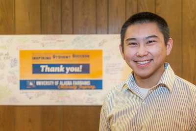 UAF scholarship recipient Ralph Sinnok takes some time out of his schedule to pose in front of a thank you poster during thank-a-donor day in the Wood Center ballroom.  Filename: DEV-13-3726-70.jpg