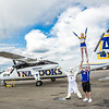 "A pair of UAF cheerleaders pose with the UAF mascot by the Era Alaska newly painted Bombardier Dash-8 which features the Alaska Nanooks colors and logo on one side, and a UAA Seawolves treatment on the other.  <div class=""ss-paypal-button"">Filename: DEV-13-3858-169.jpg</div><div class=""ss-paypal-button-end"" style=""""></div>"