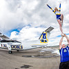 "A pair of UAF cheerleaders pose by the Era Alaska newly painted Bombardier Dash-8 which features the Alaska Nanooks colors and logo on one side, and a UAA Seawolves treatment on the other.  <div class=""ss-paypal-button"">Filename: DEV-13-3858-167.jpg</div><div class=""ss-paypal-button-end"" style=""""></div>"