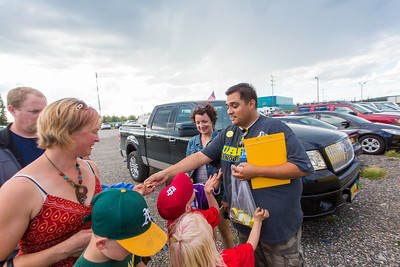 UAF Alumni Association board member Mike Campbell and fellow alum Brenda Riley hand out buttons as fans of the Alaska Goldpanners arrive at Growden Field for the annual UAF Alumni Night on July 22.  Filename: DEV-15-4583-1.jpg