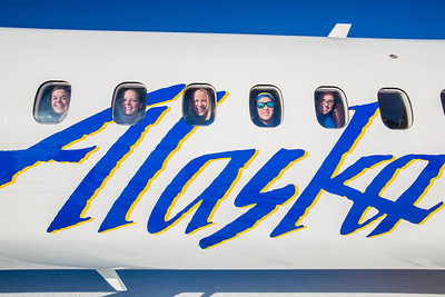 Members of the Nanooks swim team peer out the windows while touring one of the newest planes in the Alaska Airlines fleet, a Bombardier Q400 turboprop, which features the Alaska Nanooks and UAF.  Filename: DEV-14-4080-66.jpg