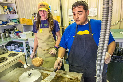 UAF Alumni Association board member Mike Campbell flips a burger to the amazement of fellow alum Kristen Sullivan during their shift in the Alumni Burger Booth at the 2015 Tanana Valley State Fair.  Filename: DEV-15-4596-017.jpg