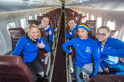 Members of the Nanooks swim team check out the seats while touring one of the newest planes in the Alaska Airlines fleet, a Bombardier Q400 turboprop, which features the Alaska Nanooks and UAF.  Filename: DEV-14-4080-62.jpg