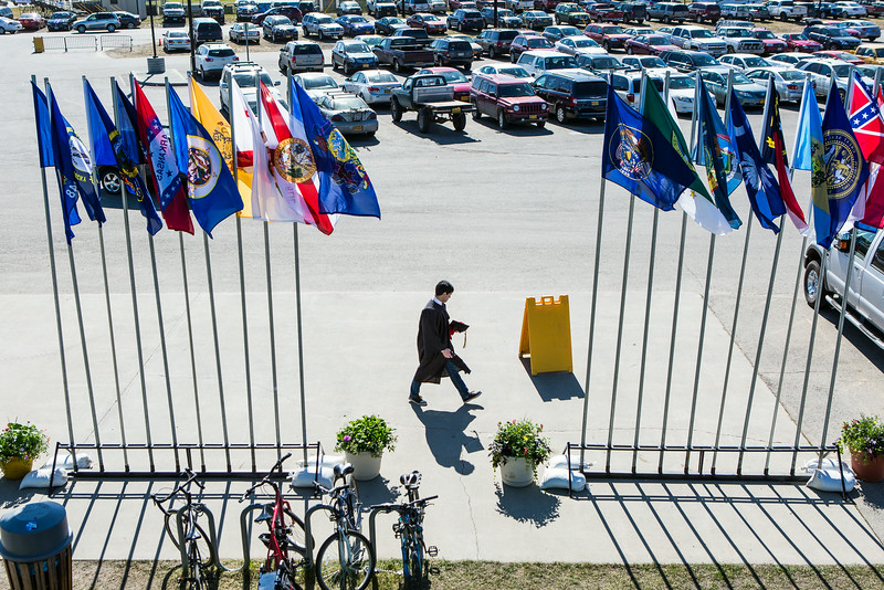 """A graduate walks toward the entrance of the Carlson Center before the 2014 University of Alaska Fairbanks Commencement Ceremony Sunday, May 11, 2014.  <div class=""""ss-paypal-button"""">Filename: GRA-14-4187-7.jpg</div><div class=""""ss-paypal-button-end""""></div>"""