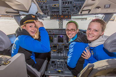 Members of the Nanooks swim team check out the cockpit while touring one of the newest planes in the Alaska Airlines fleet, a Bombardier Q400 turboprop, which features the Alaska Nanooks and UAF.  Filename: DEV-14-4080-114.jpg