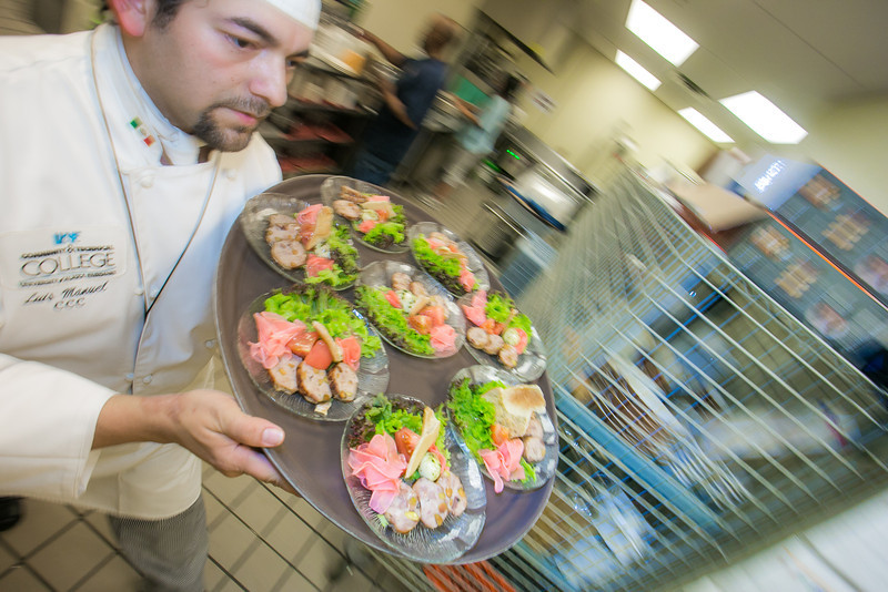 """Luis Manuel carries a tray of salads being served to guests at the annual CTC culinary scholarship banquet in the Hutchison Institute of Technology.  <div class=""""ss-paypal-button"""">Filename: DEV-12-3383-136.jpg</div><div class=""""ss-paypal-button-end"""" style=""""""""></div>"""