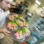 Luis Manuel carries a tray of salads being served to guests at the annual CTC culinary scholarship banquet in the Hutchison Institute of Technology.