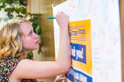 UAF scholarship recipient Teal Rogers takes some time of her schedule to add a personal message to a thank you poster during thank-a-donor day in the Wood Center ballroom.  Filename: DEV-13-3726-105.jpg